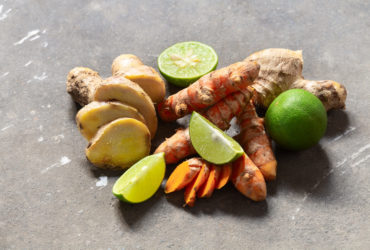 Ingredients for healthy drink from turmeric and ginger roots and lime on grey conctere background with copyspace. Immunity boosting and treatment of colds, detox, diet.